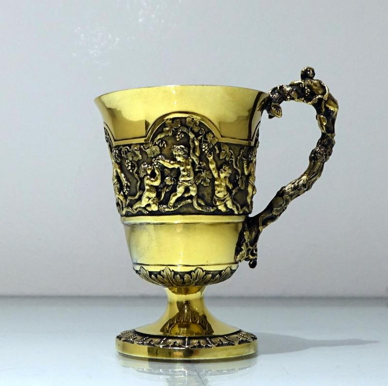 A magnificent mid-19th century silver gilt christening mug decorated with beautiful scenes of cherubs picking grapes from a climbing vine shrub which is then set on a matte background for decorative contrast. The mug has a stunning cast naturalistic