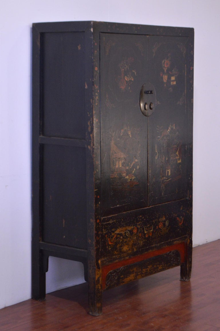 Old and elegant black lacquered Chinese cabinet in elm from the mid 19th century. 