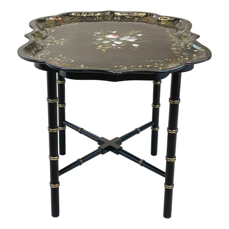 A very attractive mid 19th century black laquered Shaped papier mache tray with elegant painted & Gilded decoration housed on later faux stand With faux bamboo design legs & cross stretcher  (What better way to look after the environment than