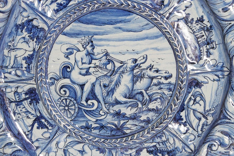 A large blue and white delft Faience charger. An elaborately shaped exterior rim surrounding a circle of alternating putti and castles. The center has a rimmed circle containing a scene of Neptune and his chariot, mid-19th century, Italy.