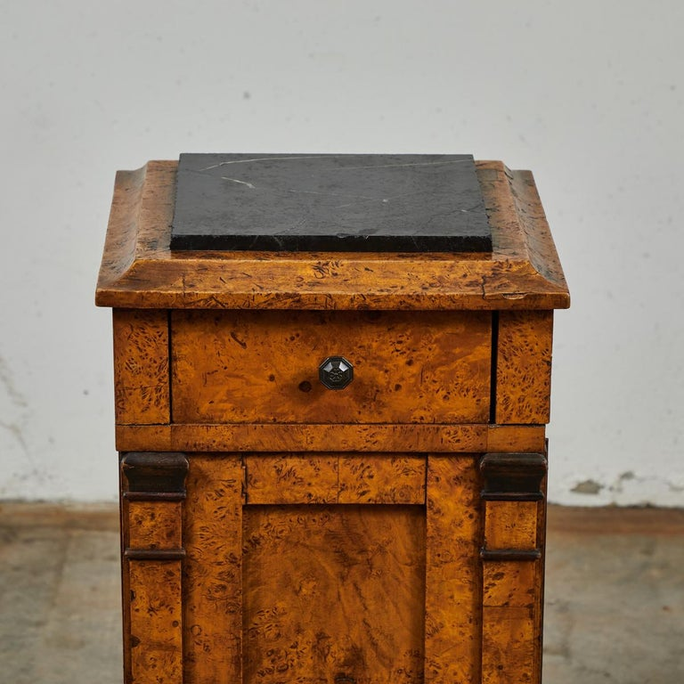 Mid-19th century burl wood stand with black marble top, single door, and drawer storage from England.