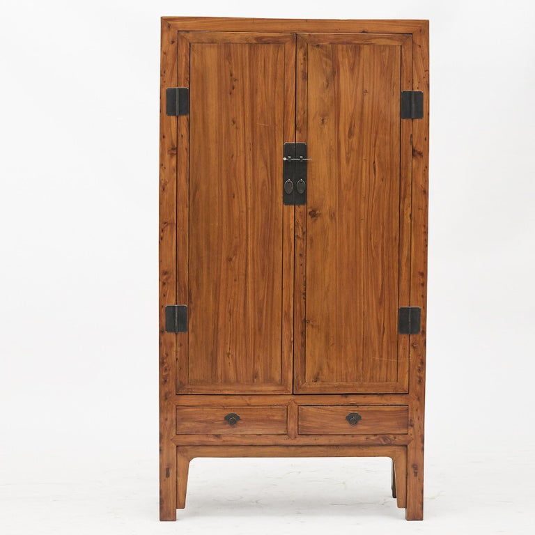 Elegant Chinese antique cabinet from Jiangsu Province, China, mid-19th century. Features two doors, beautifully accented with a rectangular brass face plate. Inside with shelves and drawers. At the bottom a pair of drawers  Peachwood has a