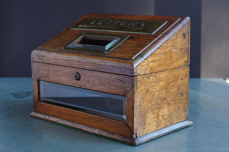 A mid-19th century country house desk top letter box, the oak body centred by a slope-front brass-mounted posting box titled