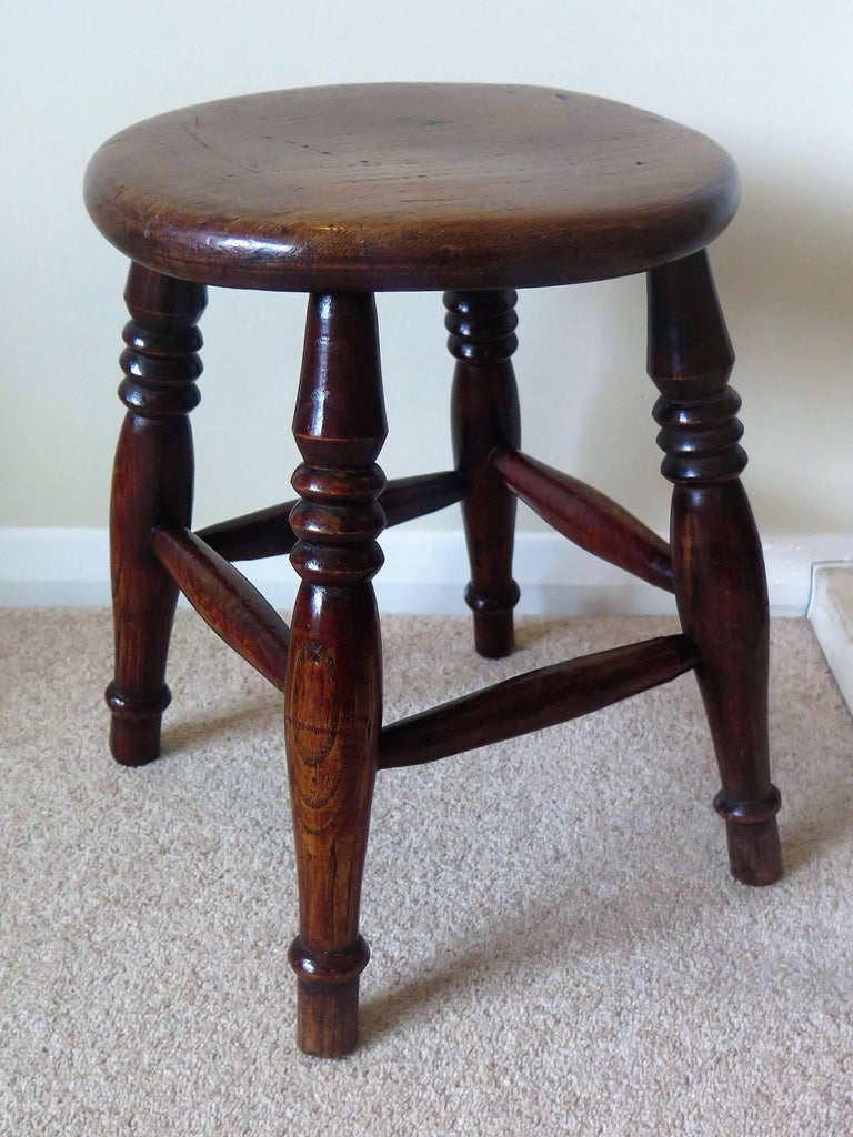 This is a lovely country stool made of Elm in Victorian England during the 19th century, circa 1850.  The elm stool has thick solid circular turned seat or top which sits on four ring turned legs with four shaped turned stretchers between the legs