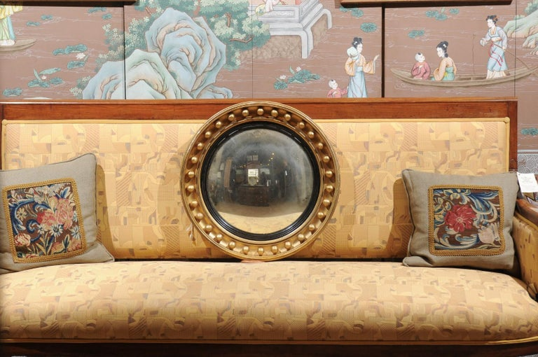 A mid-19th century English giltwood bull's eye convex mirror with ebonized border and gilt ball detail on frame.