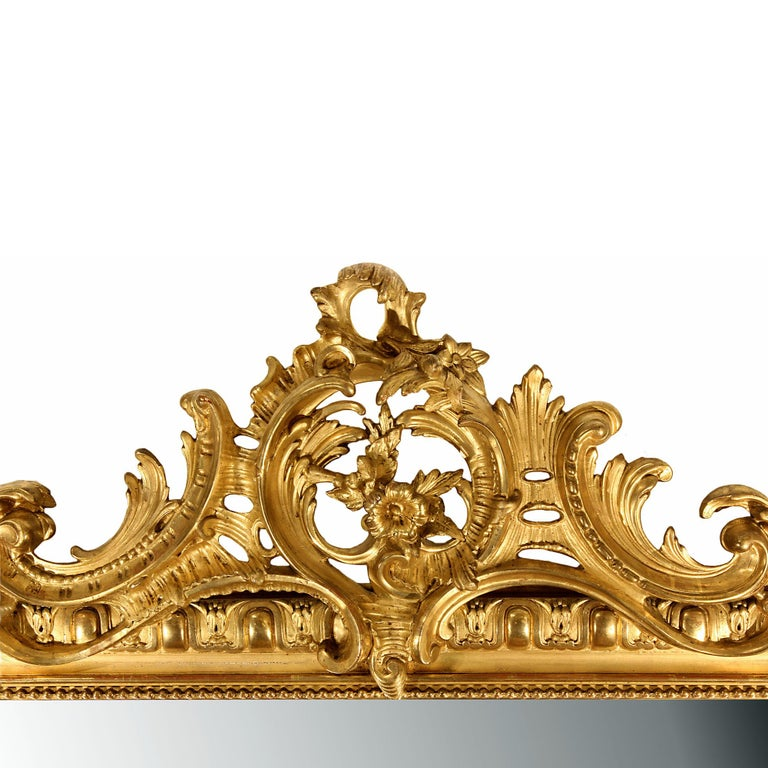 A very elegant mid-19th century French Louis XVI style giltwood mirror. The richly decorated frame has a large S scrolled acanthus leaf with flowers at the bottom. The vertical sides have an outer egg and dart design and an inner beaded trim. The