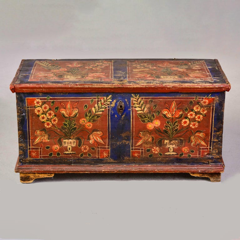Circa 1865 Romanian painted wood trunk. Great color and design with floral motif and painted panels on top, front and sides. Honest wear and fading. Painted date inside of lid is 1865. Rustic hinge hardware, dovetail construction, small internal