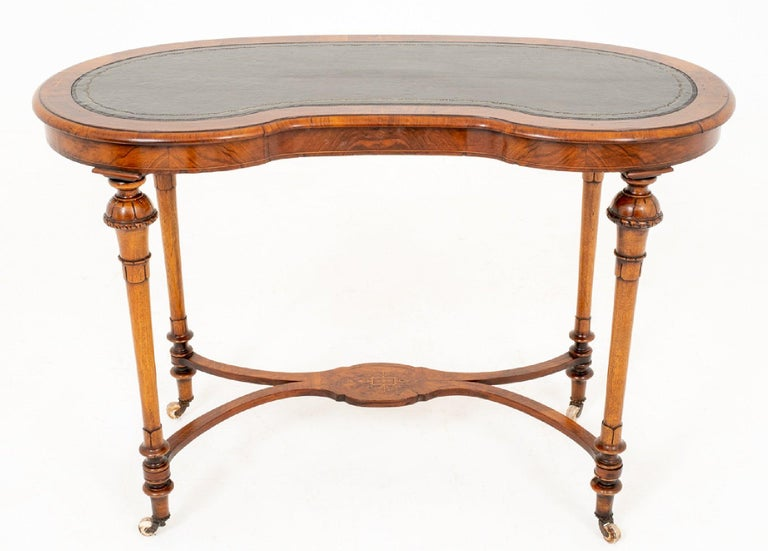 This mid-19th century ladies walnut writing table features beautifully carved and turned cabriole legs on porcelain castors with a shaped stretcher base and inset leather top. It measures 43 in – 109.2 cm wide, 20 in – 51 cm deep and 28 ¾ in – 73 cm