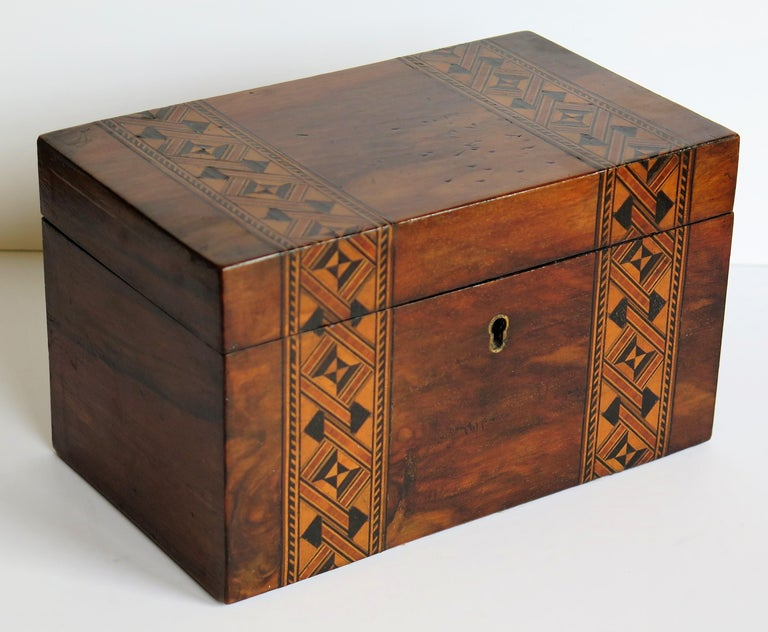 This is a very decorative and useful English lidded box, made of walnut and inlaid with a parquetry mosaic pattern, dating to circa 1840.  The box has a rectangular shape and is handmade of a well figured Walnut that has been inlaid with a