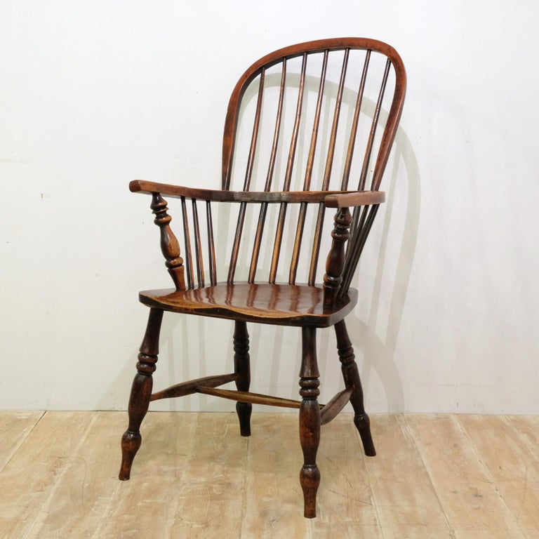 Impressive tall stick back Windsor chair, attributable to the Lincolnshire area, in ash and elm. Lots of the original red stain present and a wonderful grain pattern to the seat. Arm hoop has characterfully misshapen over its 150 or so year life.