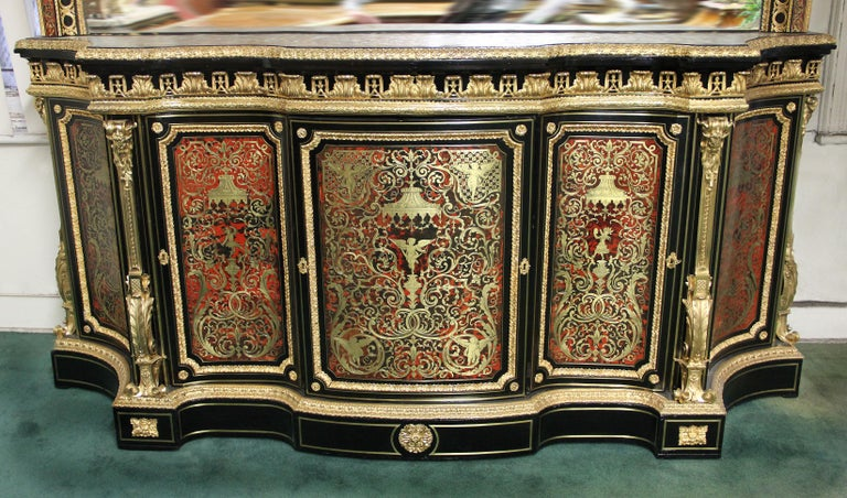 A mid-late 19th century monumental Napoleon III gilt bronze mounted ebony, red tortoiseshell and designed brass Boulle style cabinet and mirror  Each Boulle style marquetry panel with designs in the manner of Jean Bérain, the cabinet surmounted by