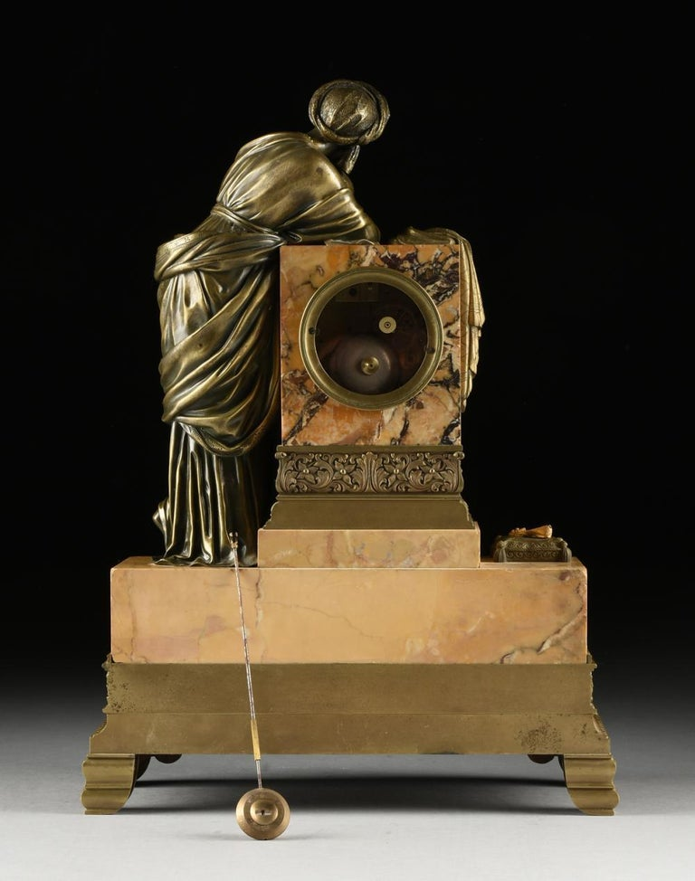Mid 19th Century Orientalist Bronze Mounted Siena Marble Mantle Clock, France. The classically robed maiden wearing an intricately detailed turban and holding a pen, while leaning on a block form pedestal draped with a shawl behind two lidded