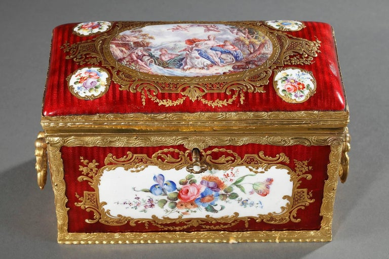 Rectangular, red enamel keepsake box with a gilt bronze frame that is very elaborately sculpted with leafy scrollwork. The body of the box is decorated with medallions featuring multicolored bouquets of flowers on a white background. The medallions