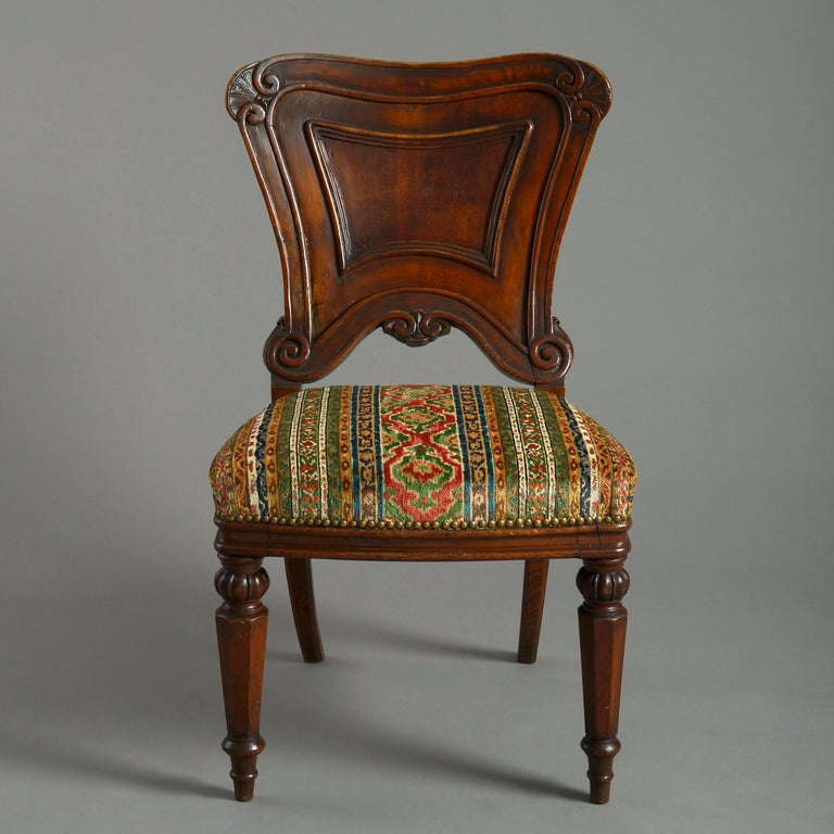 A mid-19th century Victorian Period oak side chair, the generously carved cartouche back set upon an upholstered seat and raised upon faceted turned legs.  Upholstered with Brunschwig & Fils Savonnerie Velvet Fresco Fabric.