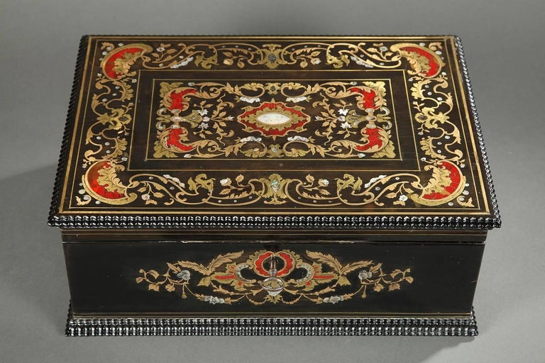 Sizeable rectangular, wooden coffer with its key. The blackened wood is inlaid with mother-of-pearl and brass. The lid and the main face of the box are richly decorated with gilded rinceau, flowers, and scrolling vegetation. The interior is lined