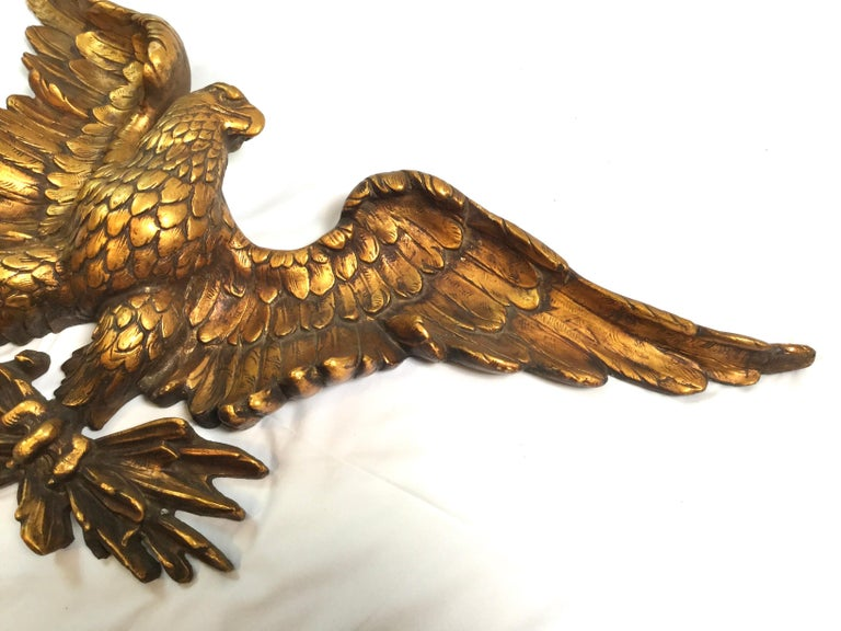An aged gold American eagle wall sculpture circa 1950s. The eagle with spread wings in a partitive pose. High relief detail.