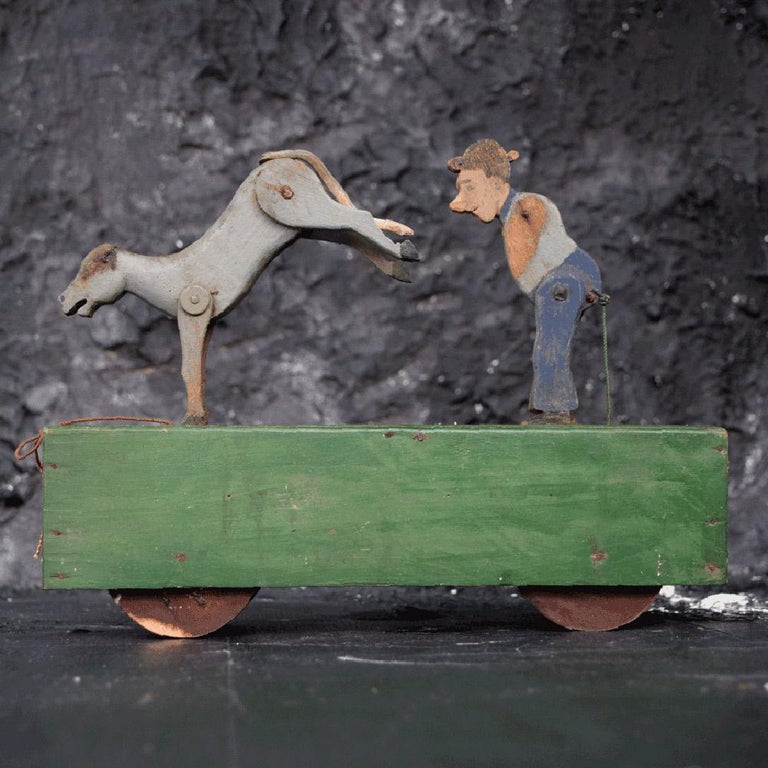 We are proud to offer a highly collectable and decorative Folk Art, self-taught child's pull along automaton toy. In its simplest form this toy is very sculptural and has lots of ages character including its simple mechanism and details carved,