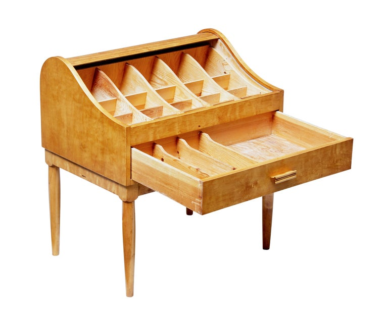 Unusual Scandinavian birch sewing table on stand, circa 1950.  Shaped top with tambour top which opens when the drawer is opened. Top section is fitted with 20 compartments of various depth. Drawer being fitted with three partitions.  Standing