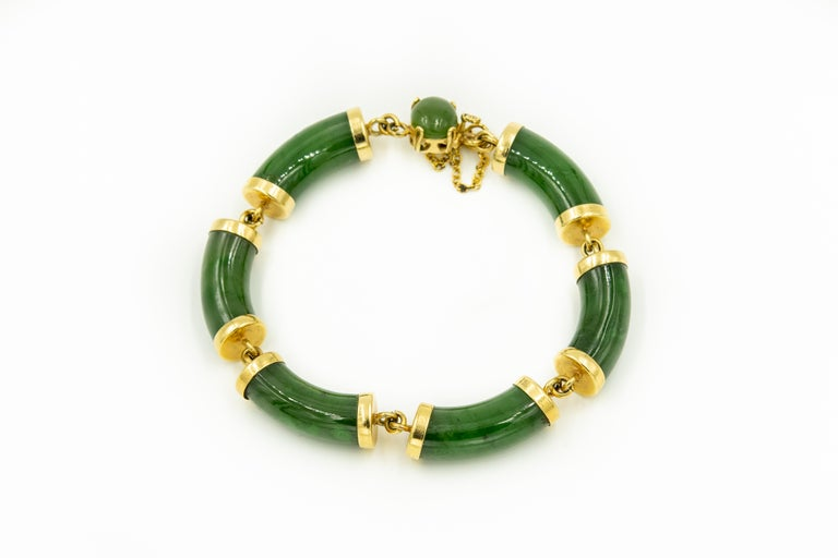 Chinese 14k yellow gold bracelet featuring nephrite jade bamboo bars with gold caps and matching clasp with an oval cabochon piece of jade on top of a 14k push button clasp.  The bracelet has an additional safety chain clasp bracelet.