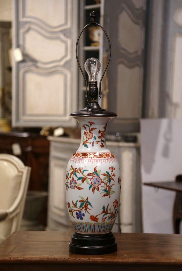 Add the perfect amount of chinoiserie into your home with this decorative porcelain lamp. Round in shape, the lamp was made by converting a vintage Chinese Famille Rose vase into a Classic table lamp. The ceramic vase is hand painted with floral