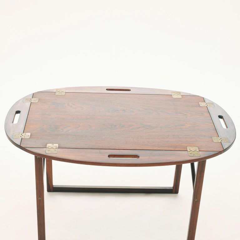 Tray table in rosewood with a removable tray top. Brass hinged edges flip up to convert to handles. 