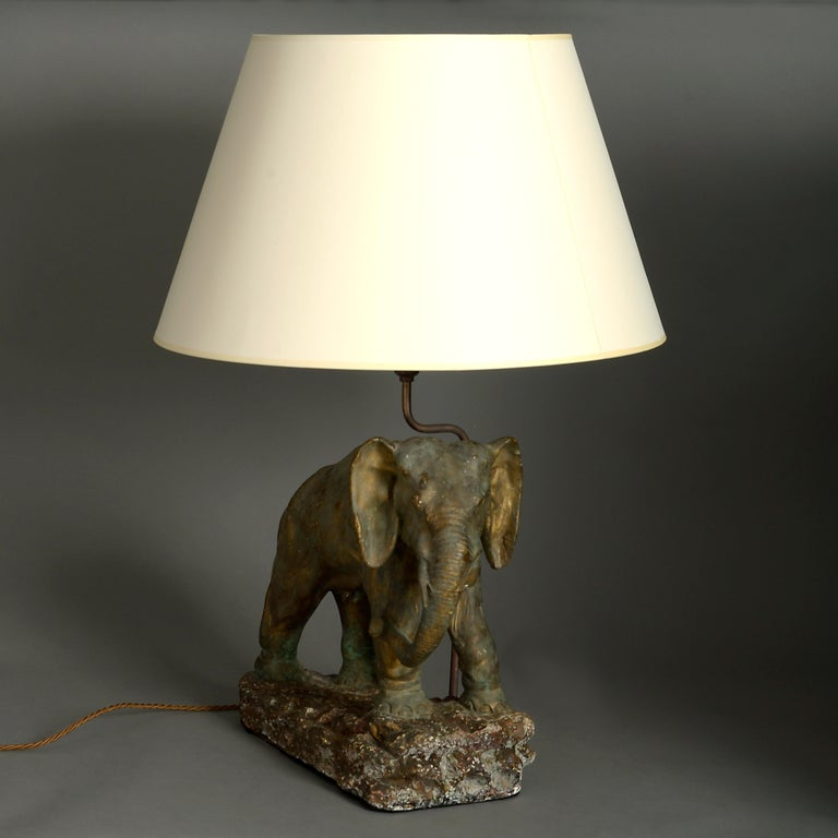 A mid-20th century cold painted elephant sculpture lamp base.  Dimensions refer only to elephant and base.  Shades available to purchase separately.
