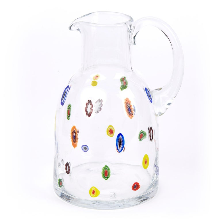 A large and impressive Italian Murano water jug in clear glass with randomly scattered colored murines within the body by Fratelli Toso. The bell shaped jug with a funnel top has a pouring handle to the neck with a wide base with a central polished