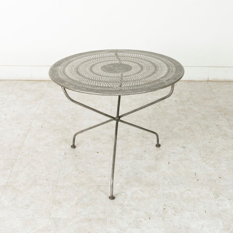 This French round outdoor garden table from the mid-twentieth century features a pierced metal top in a concentric circled pattern. The pierced top allows rainwater to pass through if the table is left outdoors. Resting on three legs that join in