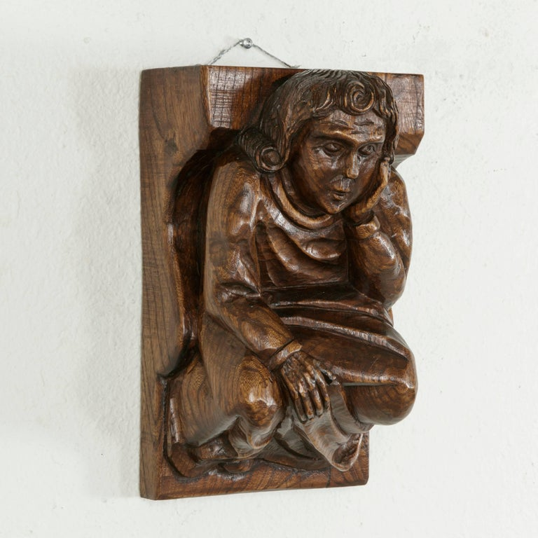 This midcentury French solid elm wall sconce was originally placed under a ceiling beam for support and features a hand carved medieval figure. Dressed in a simple robe, the medieval man rests his head on his left hand in a pensive pose while his