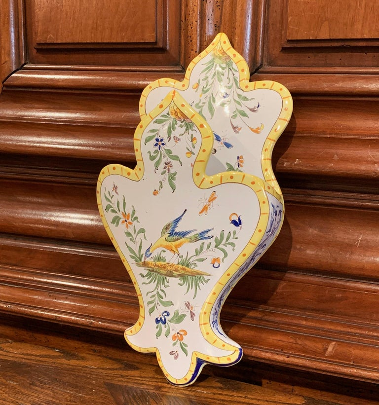 Decorate a wall or a shelf with this elegant antique ceramic letter holder from Normandy, France; crafted circa 1950, the colorful wall piece with scroll shapes features hand painted decorations including bird, flowers and foliage. The faience piece