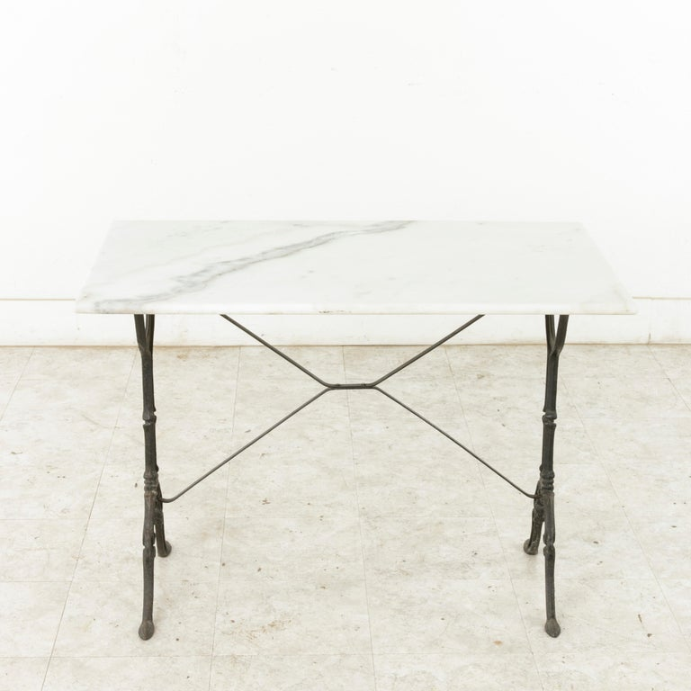Originally used in a French brasserie during the mid-twentieth century, this cast iron bistro table or cafe table features a solid white marble top with grey veining. Scrolled iron legs support the top and are joined by an X-stretcher that provides