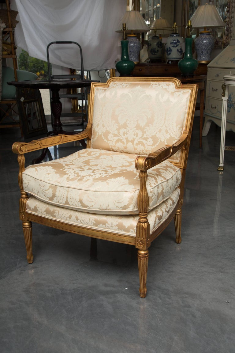 This is an interesting pair of stylized giltwood French Louis XVI stylized armchairs. The dog-eared top rail is over a fully upholstered back and an upholstered loose cushion seat flanked by out-scrolled arms. The chairs are supported by round