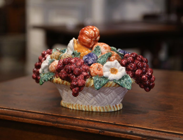 Decorate a tabletop with this colorful, majolica basket composition. Crafted in France circa 1960, the centerpiece features a realistic assortment of fruits and vegetables in high relief set inside a white basket decorated with a weave motif. The