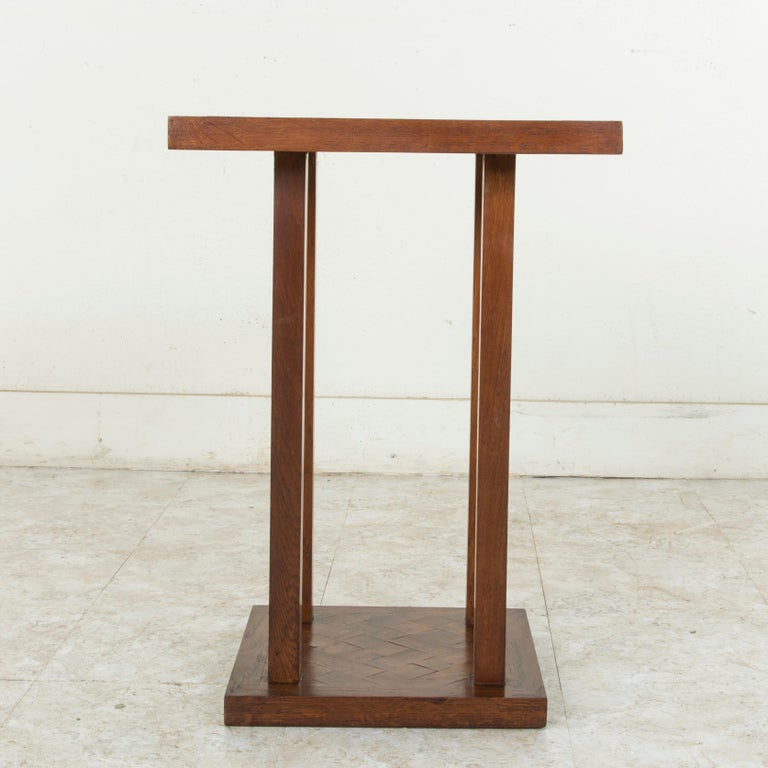 This mid-20th century French oak side table features a diamond pattern marquetry top made from one inch thick blocks. The square top is supported by four square legs that join to a lower platform. The lower platform repeats the diamond marquetry