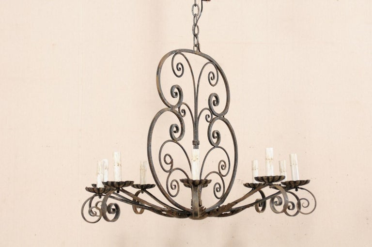 A French ten-light scrolling iron chandelier from the mid-20th century. This vintage chandelier from France features a decorative upper body, which is thinly profiled to be more visible from two opposing sides, fashioned from beautiful scrolling