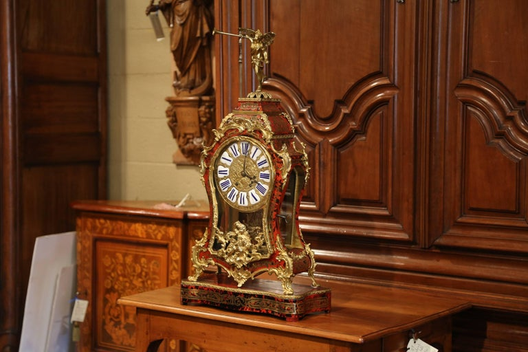 This important, vintage Boulle mantel clock was created in France, circa 1950. Standing on the original base, the clock has bronze scrolled feet and decorative mounts; it features an arched pediment surmounted with a gilt bronze cherub playing the
