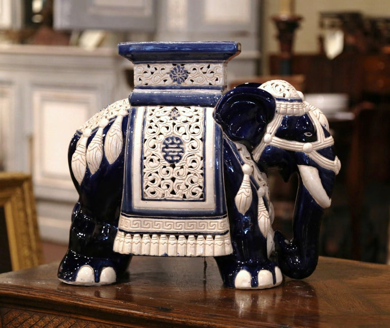 This interesting, porcelain garden seat was found in France. Crafted, circa 1950, the faience seating is in the shape of an elephant, which is heavily decorated in oriental finery. The mammal has a rectangular seat at the top, and is hand painted in