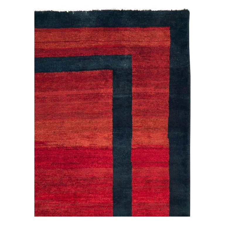 A vintage Persian Mahal accent rug in the Art Deco style handmade during the mid-20th century with a solid red field and border divided by solid dark blue graphic lines that read dark blue from the light side and black from the dark side of the