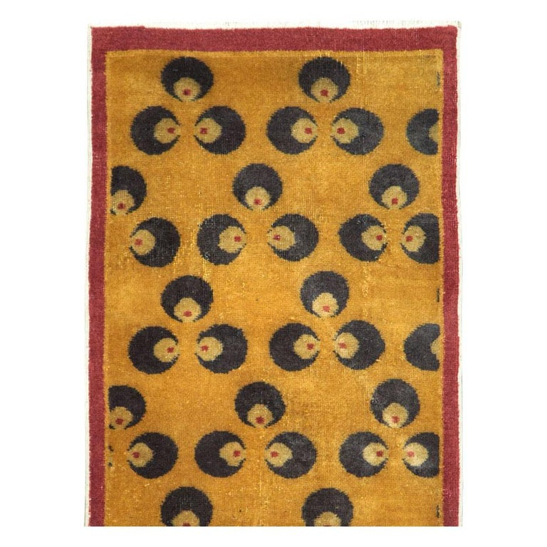 A vintage Turkish Anatolian Art Deco rug handmade during the mid-20th century. The ancient Buddhist Chintamani (often spelled Cintamani) design in a very dark midnight blue sits atop a goldenrod field and enclosed by a thin solid maroon border.