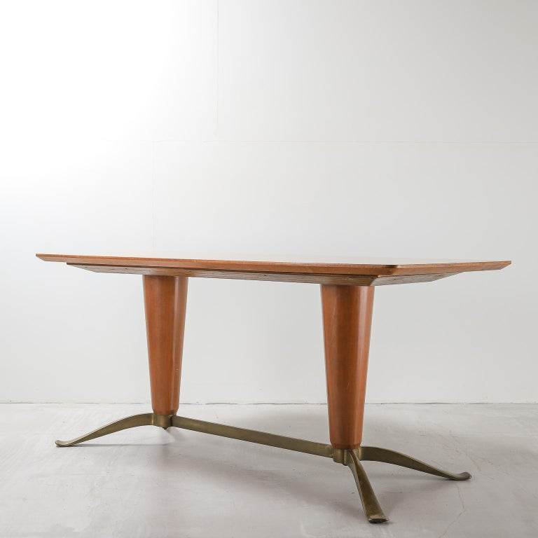 A dining table in bright, honey tone wood, circa mid-20th century, with a table top featuring a starburst pattern at its centre, sitting on two inverted conical pedestals. Four brass feet with stretcher extend from the pedestals. Attributed to Paolo