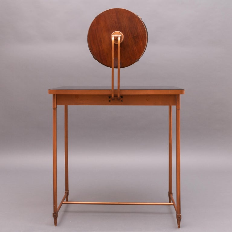 Copper vanity table with its original black glass top. One-drawer. Round mirror with a wooden base. Brass details.