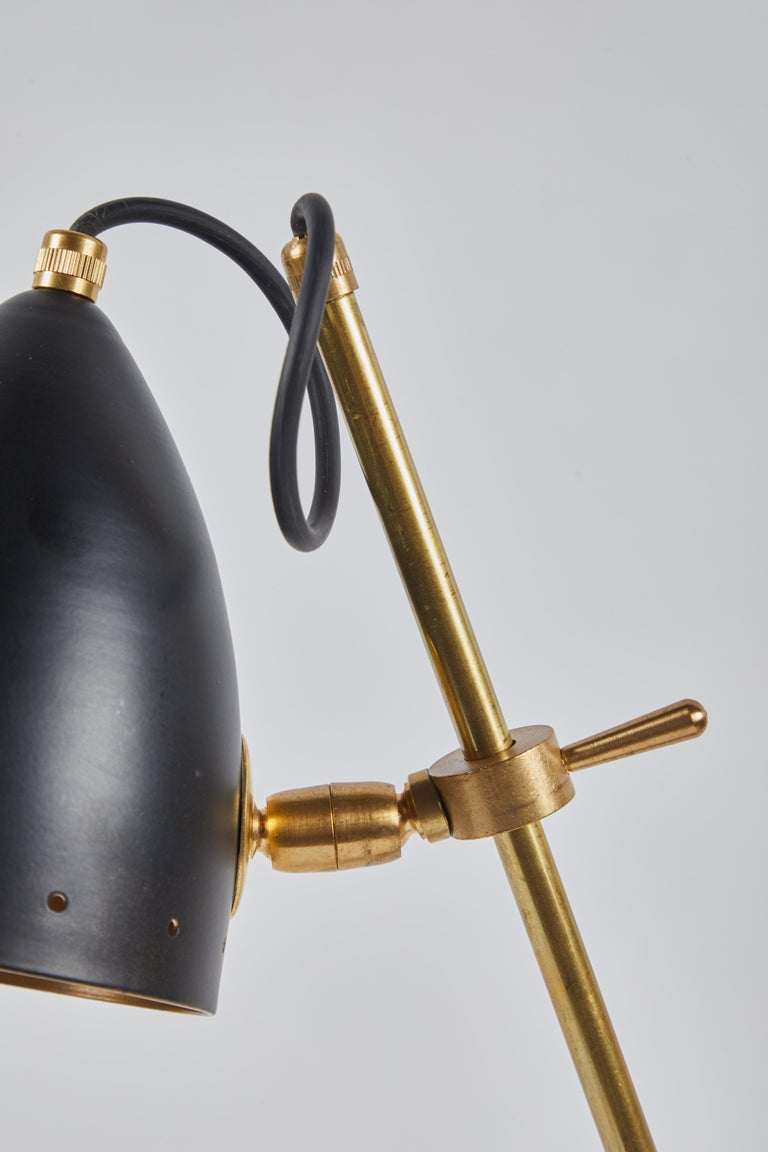 Italian midcentury articulated brass lamp on marble base with matte black shade.