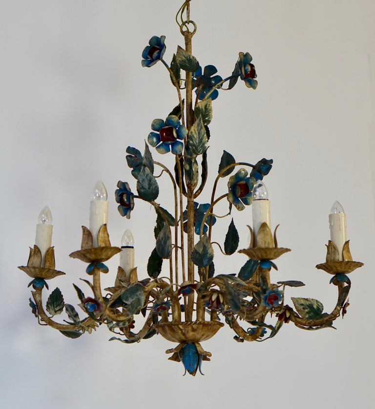 This elegant, vintage chandelier was crafted in Italy, circa 1950. The charming hanging light fixture has six lights and is embellished with realistic flowers and green leaves. The round chandelier is in very good condition and has its original