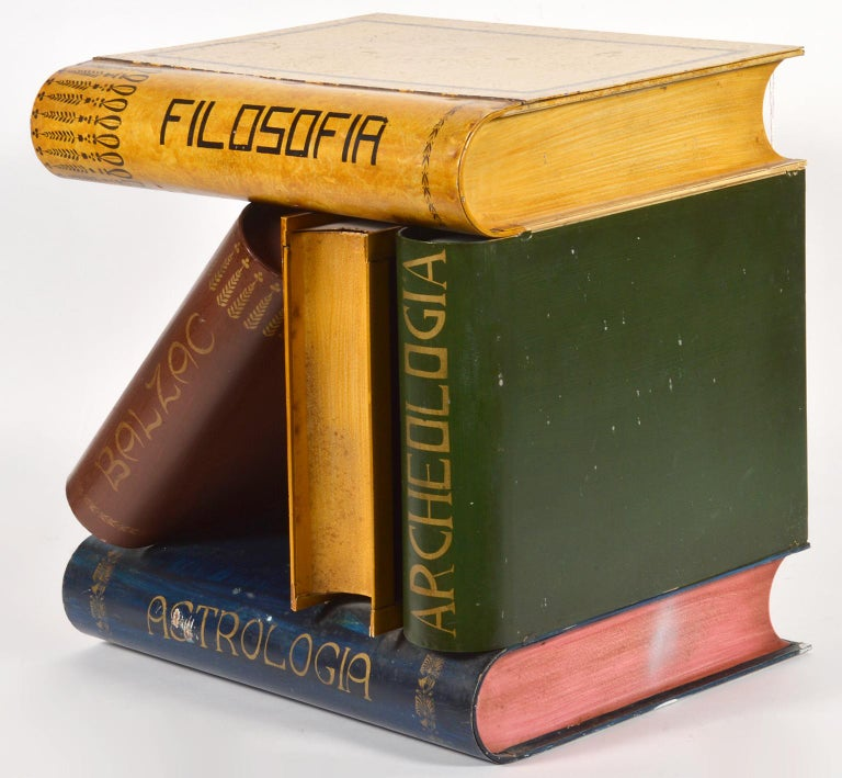 This sculptural table features 5 large faux books with titles in a composition involving one leaning book. It is made of steel tole and painted on all four sidess and the top opens up to a small storage box.