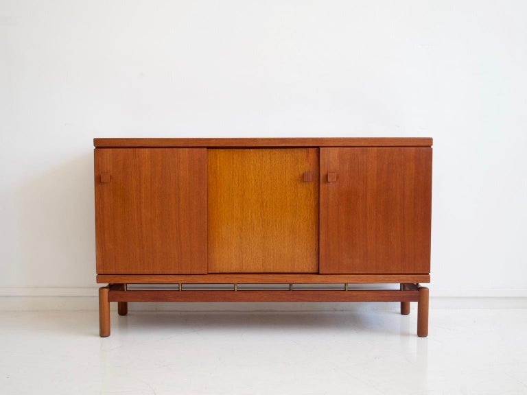 Sideboard made of teak wood with sliding doors and brass details. Manufactured and labeled by La Permanente Mobili Cantù.