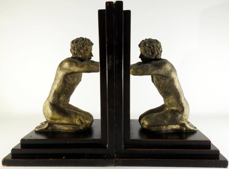 A pair of kneeling men are gazing in their respective mirrors in this pair of midcentury bookends. The nude men have rustic details and are finished in an antique gold color. They are mounted on stair step wooden bases. The bottoms and sides are