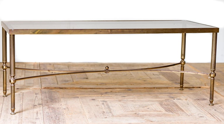 A midcentury Hollywood Regency brass framed coffee table with smoked glass top raised on reeded brass column supports.