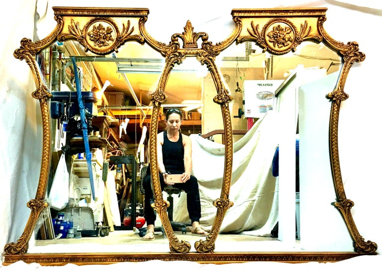 Mid-20th Century Monumental Stunning & Ornate French style carved gilt wood triptych large wall mirror. Measuring at 5.5 feet in length, this large three section hand carved gilt wood mirror  features a classic and timeless floral, acanthus leaf and
