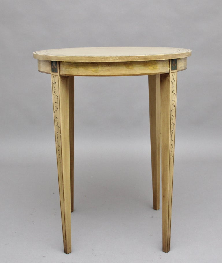 A decorative mid-20th century painted table, the circular top having a boarder decorated with a painted floral design, standing on square tapering legs decorated also with a floral pattern, circa 1960.