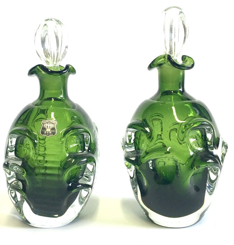 Mid-20th century modern pair of Swedish cut crystal liquor decanters by Bo Borgstrom for Aseda. The pair differentiates in size, slightly. The smaller decanter is smaller by .50